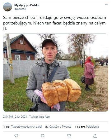 Zdjęcie zTT przedstawiające wcentralnym miejscu mężczyznę trzymającego bochenki chleba wrękach. Zanim widać drewniany dom, mur, starszą kobietę aw oddali kilka osób.