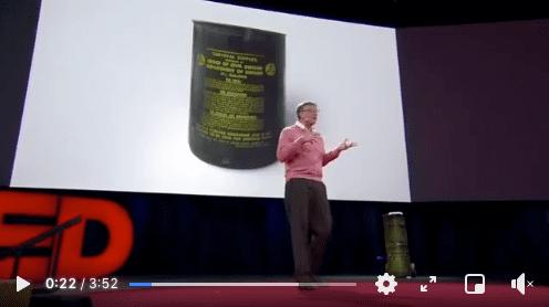 Stopklatka filmu zwystąpieniem Billa Gatesa podczas konferencji w2015 roku - mężczyzna przemawia, natelebimie zanim prezentowane jest zdjęcie zpuszką.