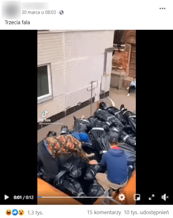 Zrzut ekranu wpisu naFacebooku naprywatnym profilu internauty zdołączonym nagraniem mężczyzn układających worki zciałami naprzyczepie ciężarówki.