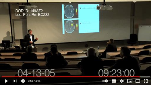 Kadr zfilmu wwysokiej rozdzielczości, naktórym mężczyzna podczas spotkania wsali wykładowej mówi oszczepionkach dlafundamentalistów religijnych - widać, żenie jest to Bill Gates. Wtle slajdy ze zdjęciami rentgenowskimi mózgu człowieka.