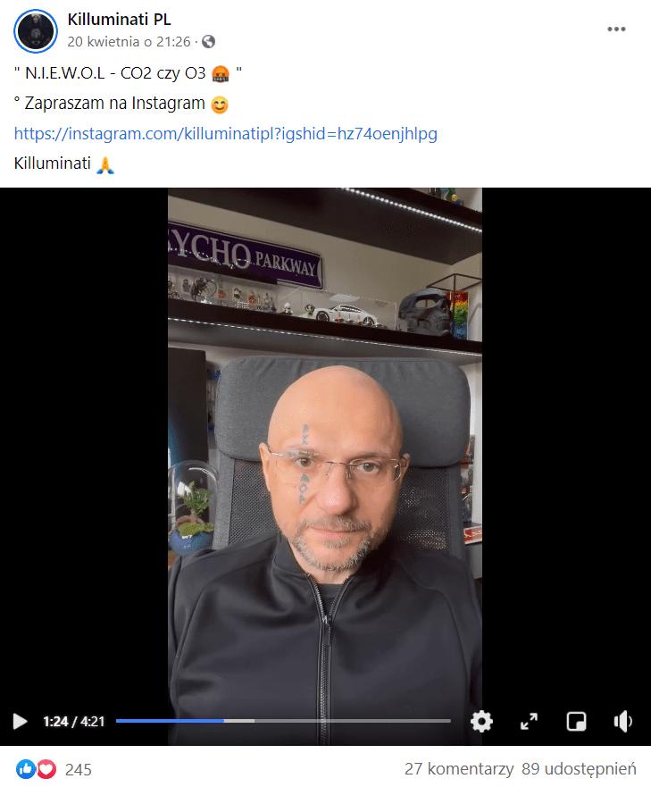 Zrzut ekranu wpisu naFacebooku naprofilu Killuminati PL, naktóry zareagowało ponad 200 osób. Dowpisu dołączono nagranie pozyskane zprofilu N.I.E.W.O.L. naInstagramie. Naujęciu uwiecznionym nazrzucie ekranu widoczny jest bezwłosy mężczyzna - Konrad Niewolski - ztatuażem znapisem walfabecie runicznym przecinającym pionowo linię oka. Siedzi on nakrześle wpomieszczeniu. Wtle widać ludziki ikonstrukcje zklocków lego, atakże kilka innych przedmiotów.