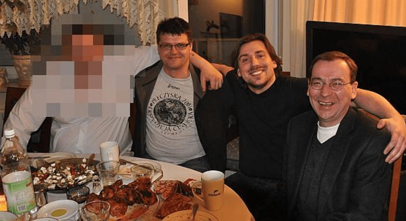 Zdjęcie przedstawiające Mariusza Kamińskiego, Tomasza Kaczmarka, Macieja Wąsika iniezidentyfikowanego mężczyznę. Wszyscy siedzą przyimprezowym stole itrzymają się przyjacielsko zaramiona.