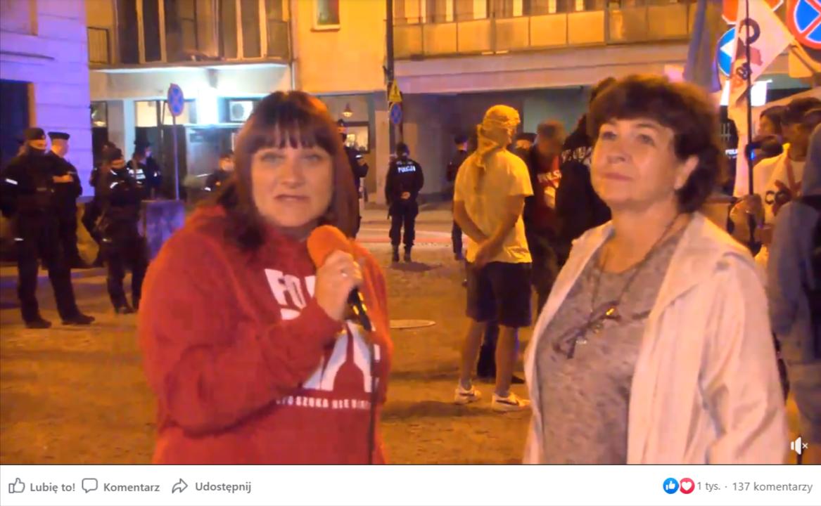 Zrzut ekranu zFacebook Watch, wktórym zamieszczono nagranie zJustyną Sochą idr Dorotą Sienkiewicz. Nanagraniu widać obie kobiety przeprowadzające rozmowę wieczorną porą natle grupy osób ztransparentami orazpolicji.