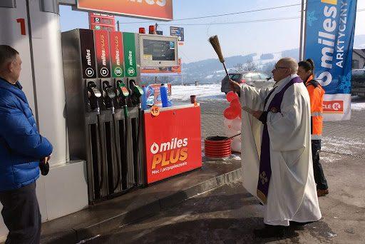 Zdjęcie księdza święcącego dystrybutor paliwa nastacji benzynowej. Duchowny ubrany jest wbiały habit, został uchwycony wtowarzystwie dwóch innych osób. Wtle widać ośnieżone pola iwzgórza.