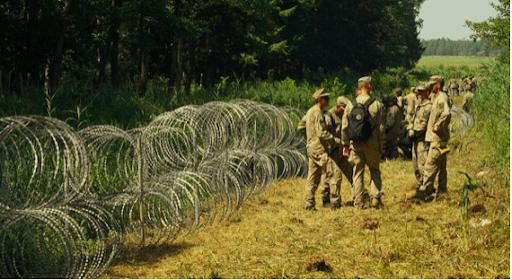 Oryginalne zdjęcie zrobione nagranicy litewsko-białoruskiej. Widać nanim żołnierzy stojących przydrucie kolczastym ustawionym nagranicy lasu.