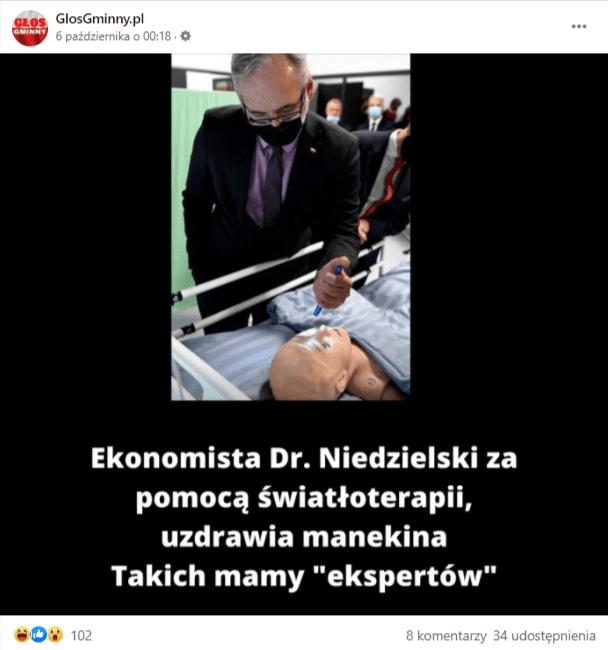 Zrzut ekranu posta naFacebooku. Grafika przedstawia ministra zdrowia Adama Niedzielskiego, który, ubrany wczarny garnitur, fioletową koszulę, ciemnofioletowy krawat iczarną maskę, stoi nadłóżkiem, naktórym leży manekin iświeci latarką wjego oko.